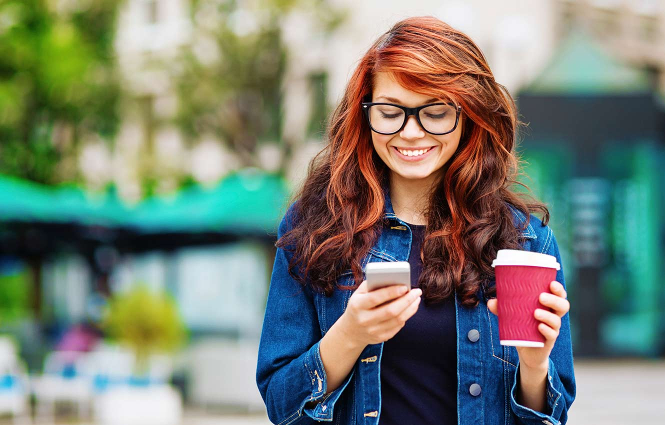 Woman outside holding coffee and using phone.