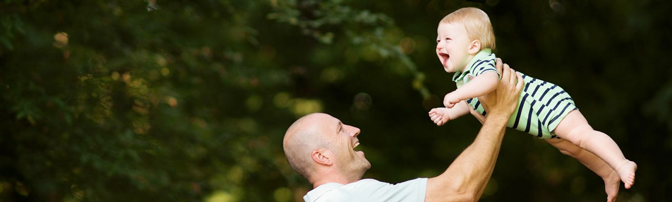 smiling-father-holds-laughing-boy-toddler-in-the-air